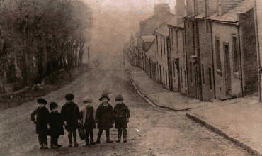 A group of small children stand at the top of Montgomery Street in the early 1900s